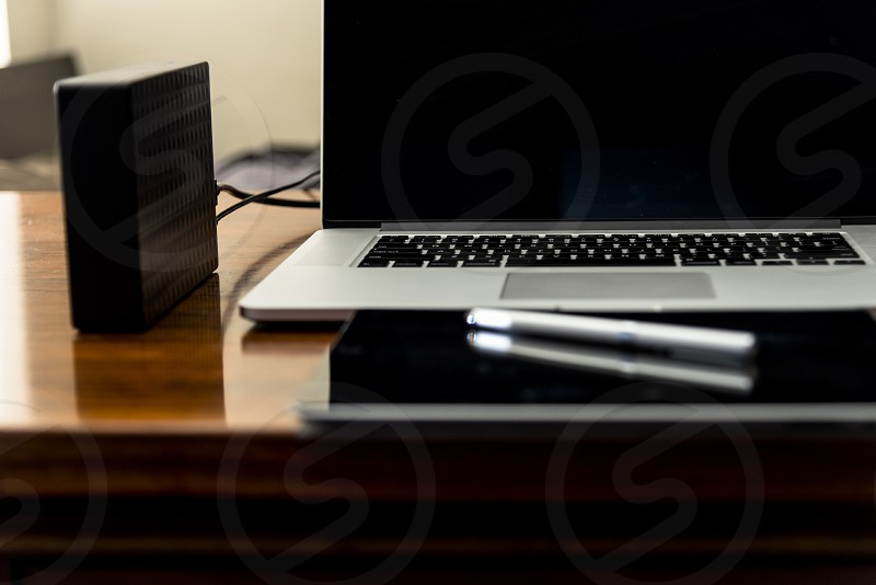 External hard drive on desk with laptop computer. photo