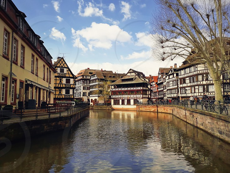 Colorful romantic city Strasbourg France Alsace. Traditional timbered houses near the river. Medieval home facade historic town. Beautiful idyllic architecture reflected in water in a sunny day. photo