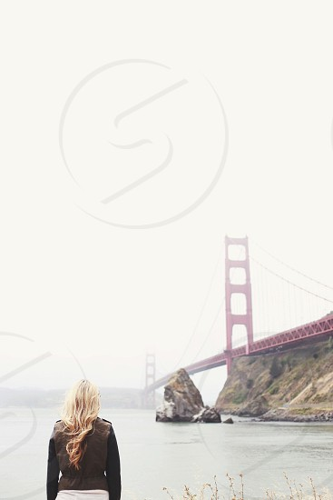 woman standing by golden gate bridge photo