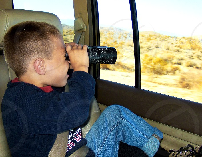 Little boy in the back seat of a car looks through the car window with binoculars at what is outside photo