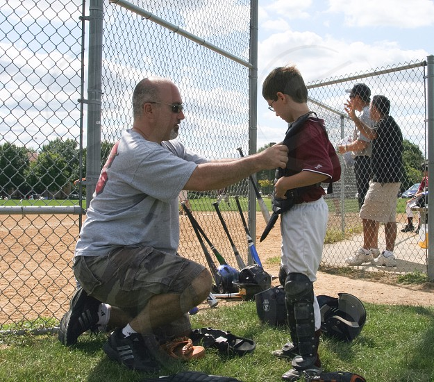 man in grey shirt camouflage shorts fixing boy wearing catcher's uniform red baseball jersey photo