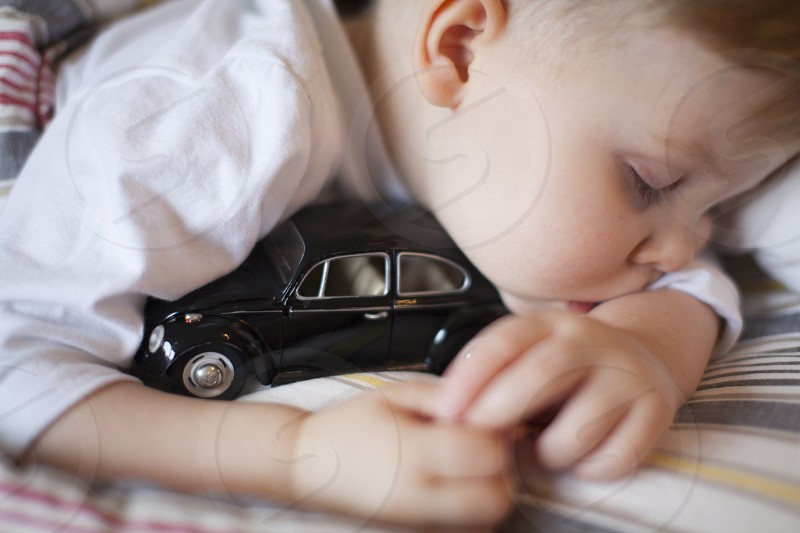 Toddler sleeping with his car. photo
