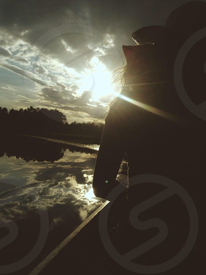 silhouette of woman wearing brown hat riding boat on calm water during golden hour photo
