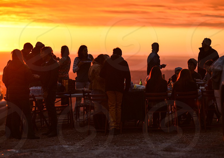 men and women sitting and standing near table below orange sky during sunset photo