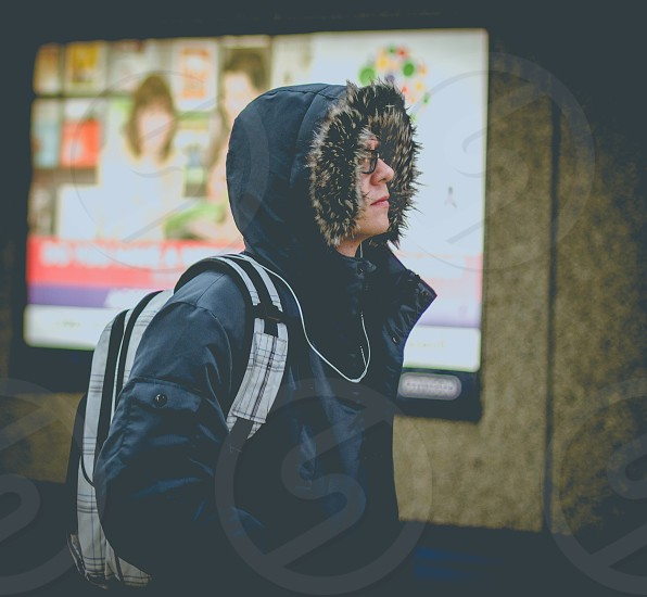 person wearing a jacket near the television photo