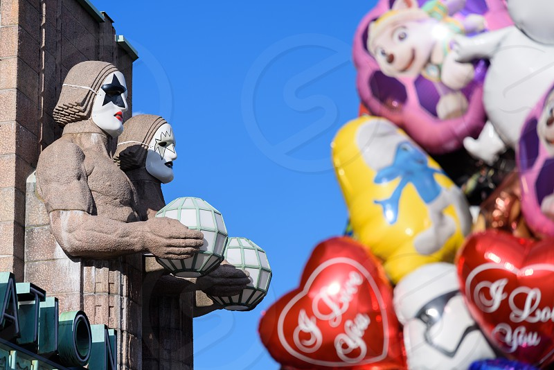 HELSINKI FINLAND - 1 May 2017: Iconic stone men statues by the side of the entrance to the Helsinki Central Railway Station decorated as wearing heavy rock band Kiss masks during First of May celebrations in Helsinki Finland with colourful balloons on the foreground. photo