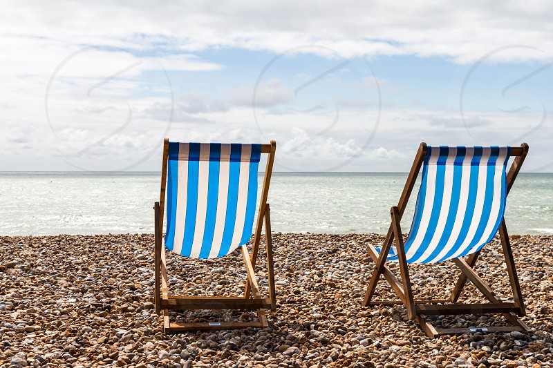 two blue and white striped folding chairs on a beach in England on a sunny day. photo