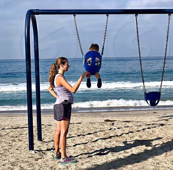 Mother Pushing Her Toddler On A Swing Set Overlooking The Pacific Ocean Vacation Mother Child Beach Swing Happy Fun Waves  photo