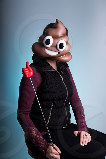 A young woman sits while wearing a smiling poop emoji mask and holding a thumbs-up on a stick.  Social Media approval like likes photo
