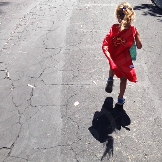 blonde haired girl wearing superman cape walking on street during daytime photo