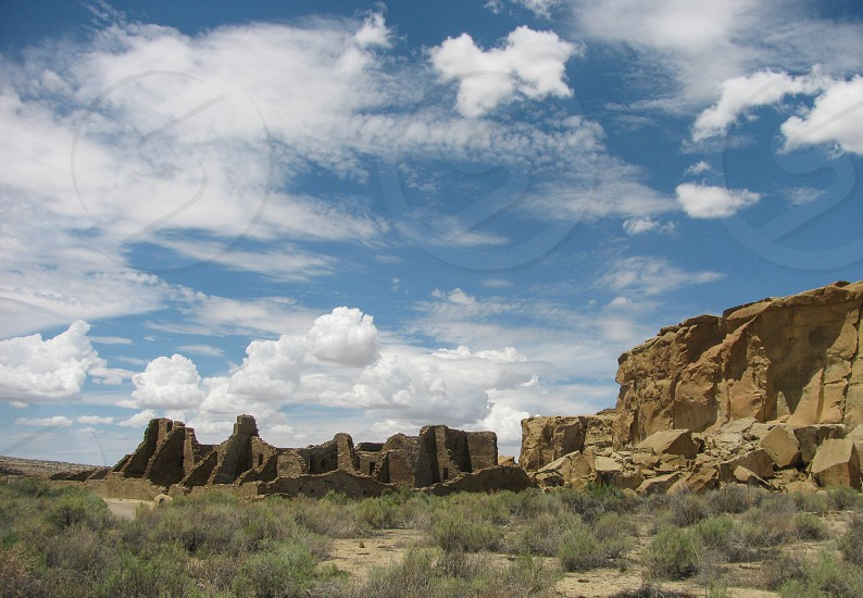 Pueblo Bonito great house in Chaco Culture National Historical Park by the canyon wall in a midsummer view with a dramatic blue sky with clouds. Built by the ancient Puebloan Anasazi culture. photo