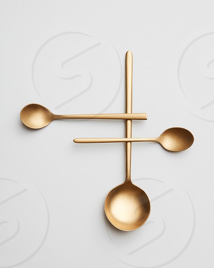 A creative composition made of different golden spoons on a gray background. Top view photo