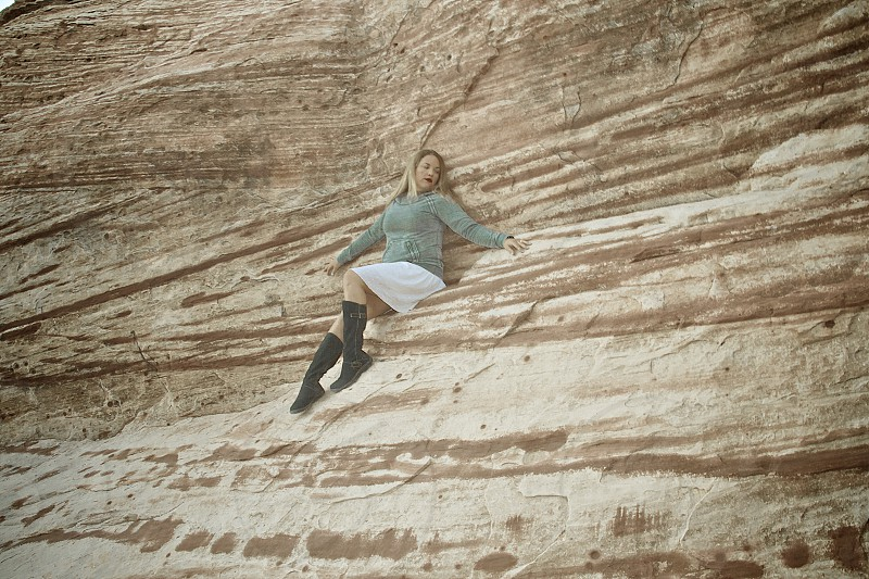 woman perched on a cliffside seat photo