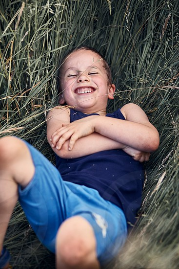 Little happy smiling boy playing in a tall grass in the countryside. Candid people real moments authentic situations photo