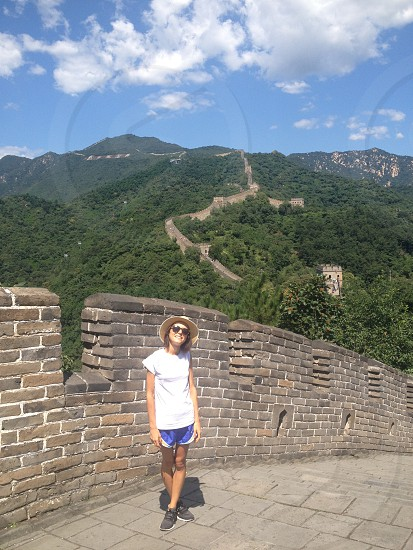 woman wearing white crew-neck shirt standing on Great Wall of China under blue sky during daytime photo