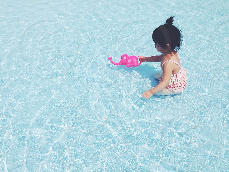 girl in red and white layered swimsuit holding pink elephant plastic toy on body of water during daytime photo