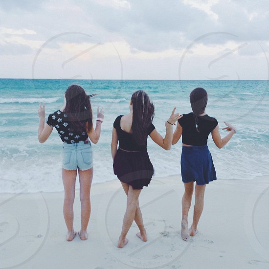 three woman looking on the ocean photo