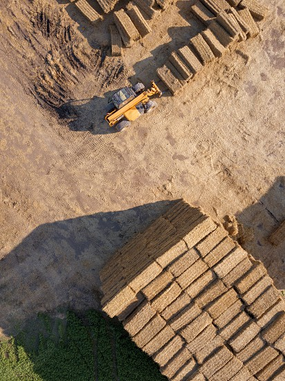 Aerial view from drone agricultural machine collecting bales of hay on a field. Farm industry. Top view photo