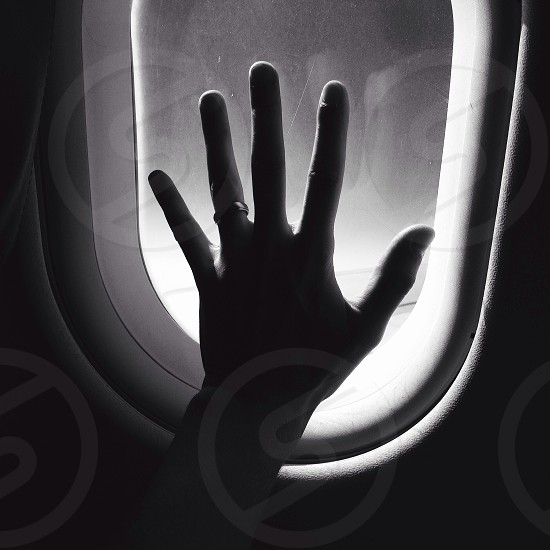 grayscale photography of person touching window photo