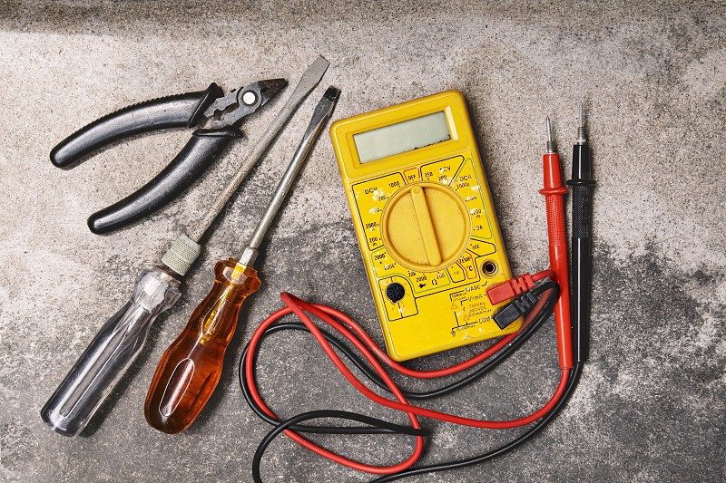DIY home electricity working tools concepts Old screwdrivers pliers and electricity voltage multimeter on dusty cement background photo