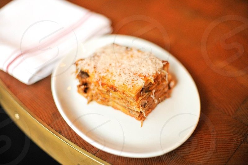 layered lasagna with shredded parmesan on a white plate photo