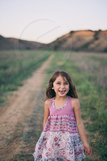 girl in floral tank dress in field smiling photo