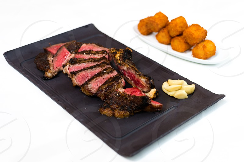 sliced pieces of steak and potatoes photo