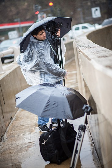 A videographer sets up a shot under an umbrella while fighting the rainy weather. photo