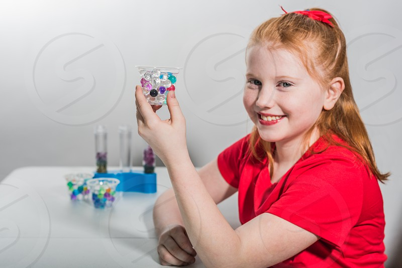 Little girl with red hair in a red shirt doing science experiments. photo