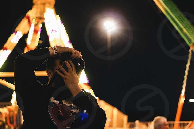 close up photo of a person using DSLR camera wearing black jacket photo