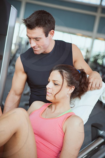Trainer helps woman in gym.  trainer gym working out exercise fitness woman man helping assistance  photo