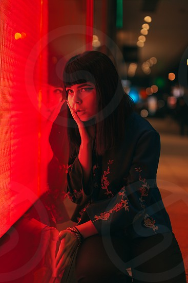 Young Japanese girl stand near neon lights and pose to the camera. Red and blue light night time street photo