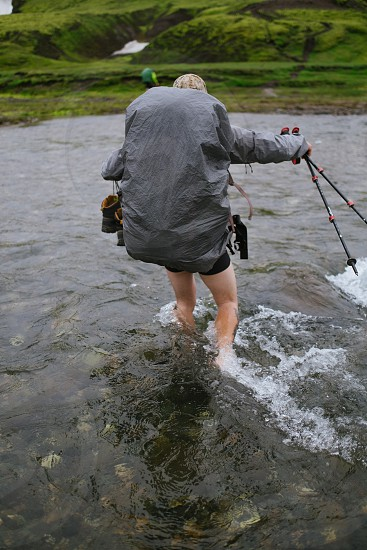 woman walking through stream with equipment photo