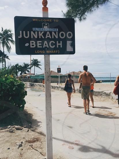 people walking near junkanoo beach road sign photo