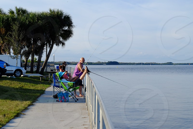 People fishing along the water front.  photo