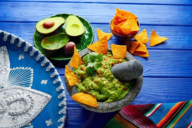 Guacamole with nachos avocado in Mexican molcajete and Sombrero hat photo