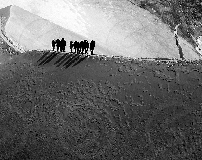 8 men silhouette walking on top of mountain  photo