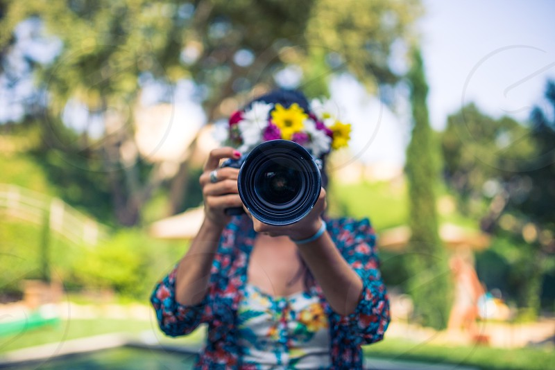 woman in red floral printed blue blazer holding black dslr camera and taking photo photo
