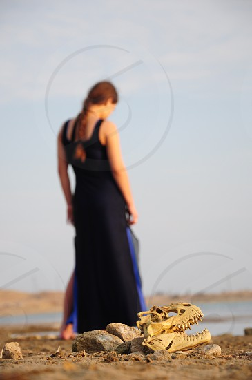 woman in long black dress standing on a desert with an animal skull on it photo