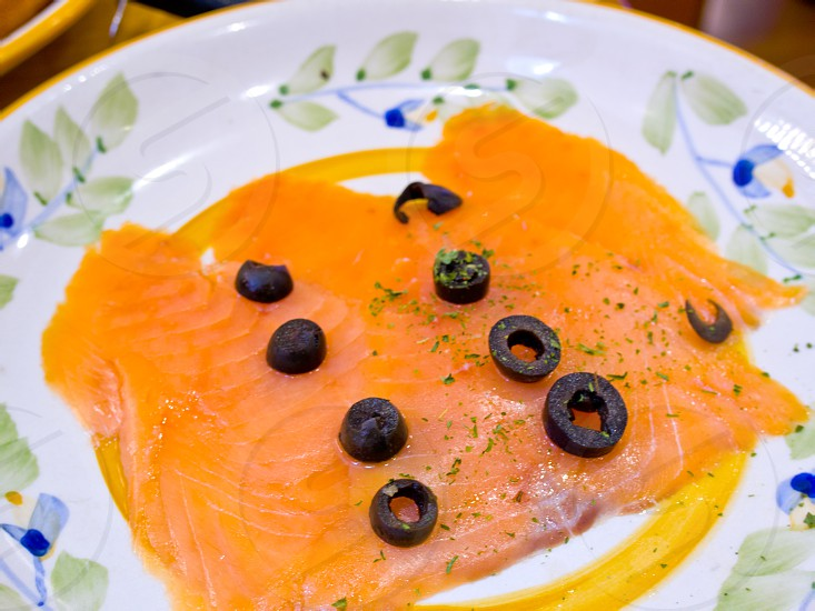 Norwegian smoked salmon with black olives on top photo