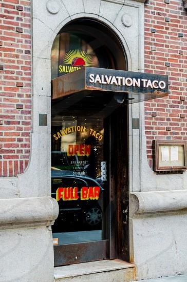 salvation taco open full bar glass door in a brick building photo