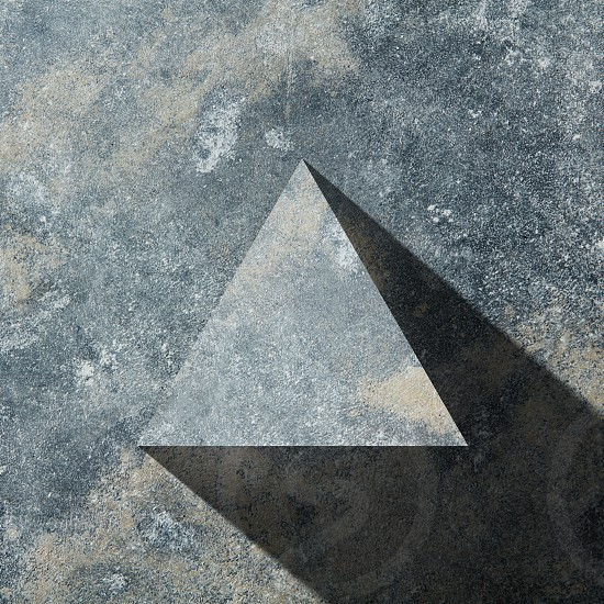granite triangle with shadow isolated on dark stone background flat lay photo