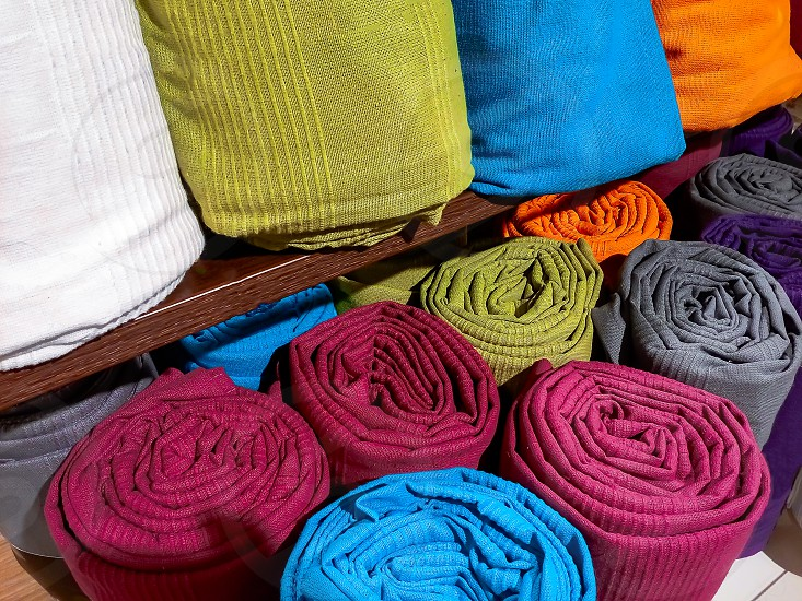 Rolled blankets and blankets of different colors photo