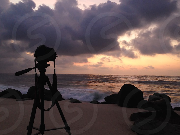 silhouette of dslr camera with tripod under gray clouds photo