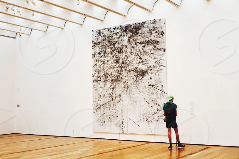man in black backpack looking at wall art photo