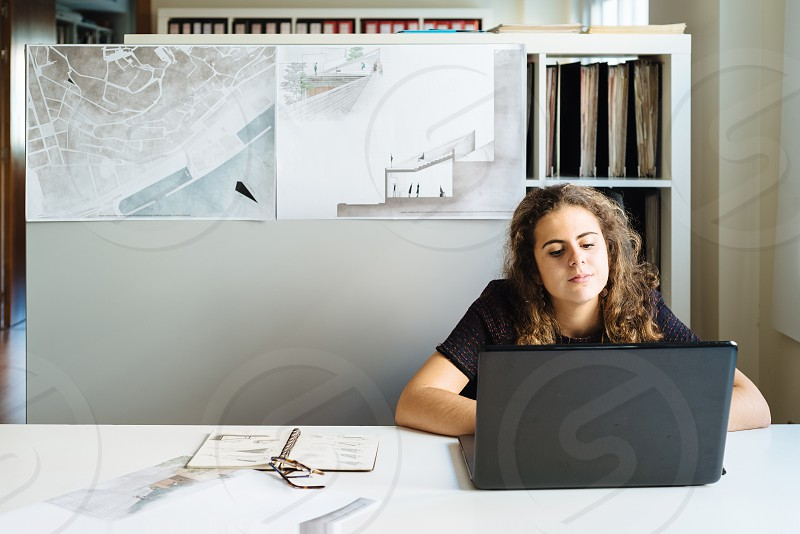 Millennial female architect working with laptop at her desk against blueprints on background board photo