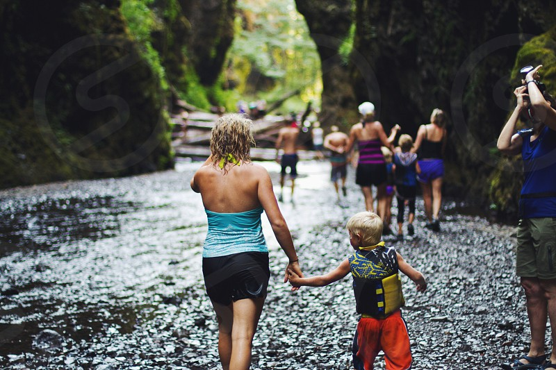 Woman and child hand in hand walking along the rocky river bank photo