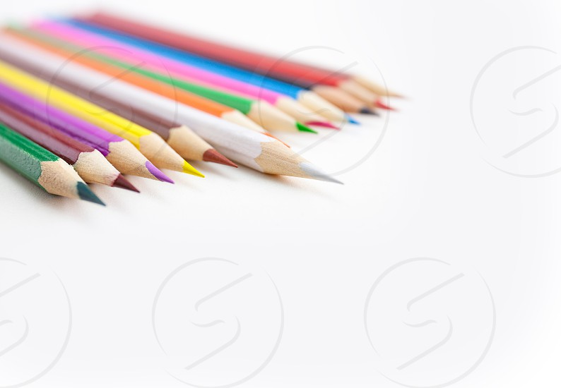 Colored crayon pencils in a row on the white desktop with selective focus on the white color tips with copy space. View from above. photo