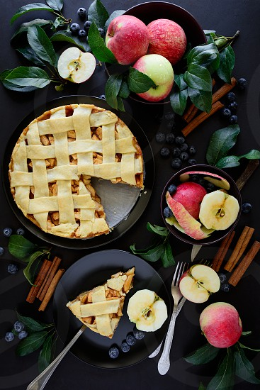 American tradition apple pie with apples blueberry and cinnamon decorated apple leaves on dark wooden background. Top view. Flat lay. Still life. photo