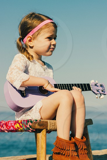 girl in white floral lace dress holding a purple acoustic guitar photo